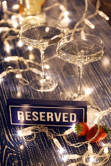 Closeup of two glasses of white wine in transparent crystal glasses, strawberries, reserved signs and light garlands