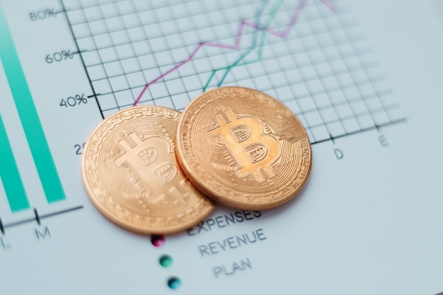 Closeup two gold bitcoins on the financial chart