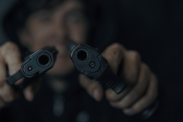 Closeup of two gun muzzles man threatens with firearm criminal with weapon two pistols in mans hands...