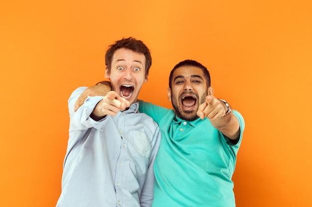 閉じる。お互いに抱き合って、指を指して、カメラを見て、叫んだり叫んだりする2人の幸せな友達。オレンジ色の背景で撮影したスタジオ