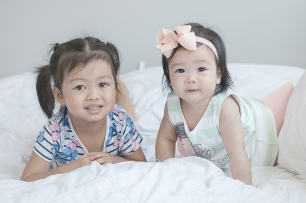 Closeup two little girls on bed Premium Photo