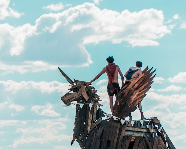 Closeup of two men standing on a unicorn statue made of planks of wood against a cloudy sky