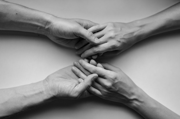 Closeup on two pairs of hands holding each other at a table