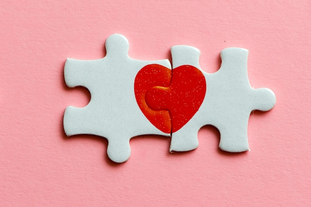 Closeup of two pieces of a puzzle with red heart on pink background