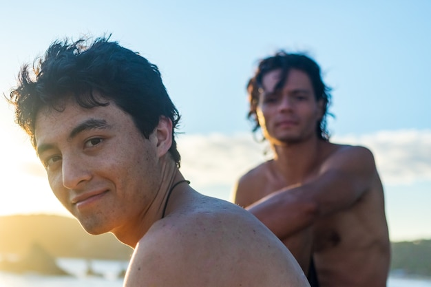Closeup of two shirtless mexican guys looking at front at the beach