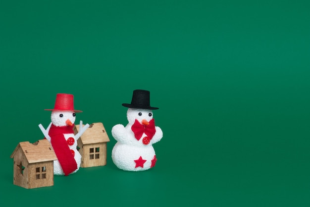 Primo piano di due pupazzi di neve e piccole case di legno come ornamenti natalizi su uno sfondo verde