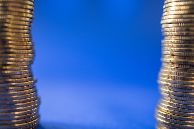 Closeup of two stack of gold coins on blue background with copy space