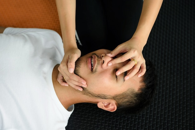 Closeup of unconscious asian man and female hands holding his nose and opening mouse