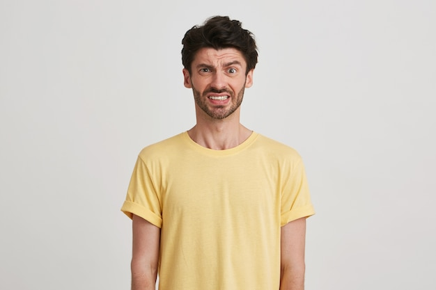 Primo piano del giovane barbuto scontento infelice che indossa maglietta gialla sembra deluso e accigliato il suo volto isolato su bianco
