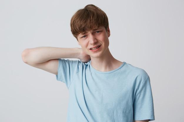 Primo piano del giovane scontento infelice con le parentesi graffe sui denti indossa la maglietta blu