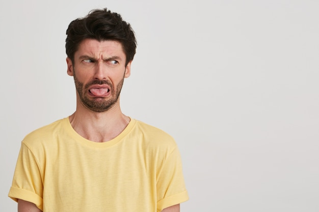 Closeup of unhappy irritated bearded young man wears yellow t shirt feels displeased, shows tongue and looks to the side isolated on white
