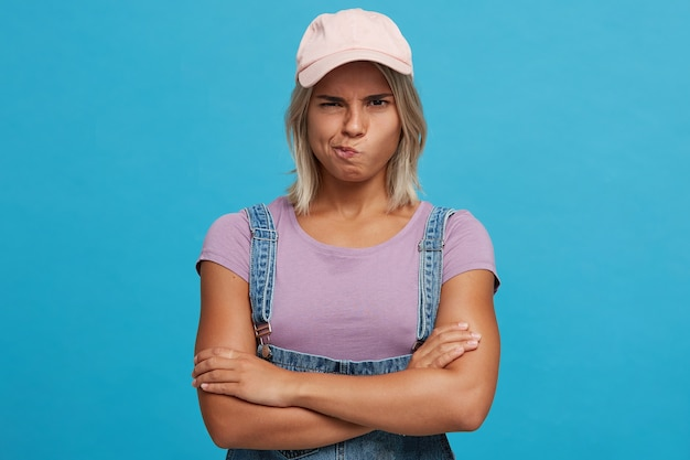 Closeup of unhappy upset blonde young woman wears pink cap, violet t shirt and denim jumpsuit looks displeased and keeps arms crossed isolated over blue wall