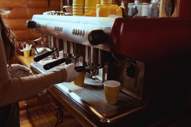 Closeup of unrecognizable barista making coffee in professional coffee machine