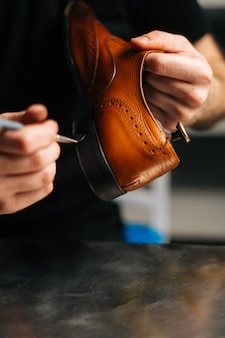Closeup of unrecognizable shoemaker painting heel and sole of light brown leather shoes with brush d...