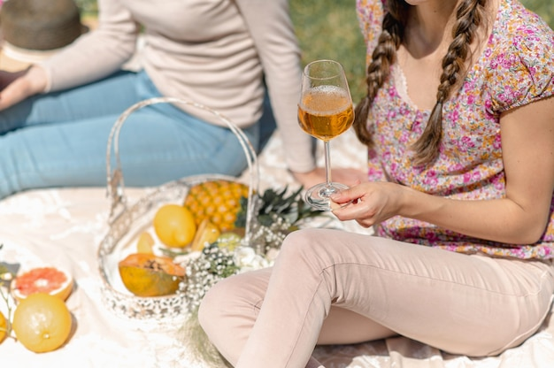 Closeup unrecognizable woman holding a wineglass full of white wine. glass with droplets. females sitting on a blanket having picnic with variety of fruits on background.