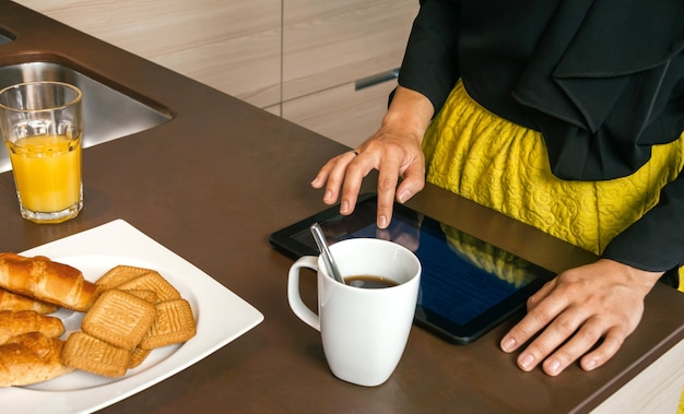 Closeup of unrecognizable woman ready to go out using electronic tablet while having fast breakfast in the kitchen