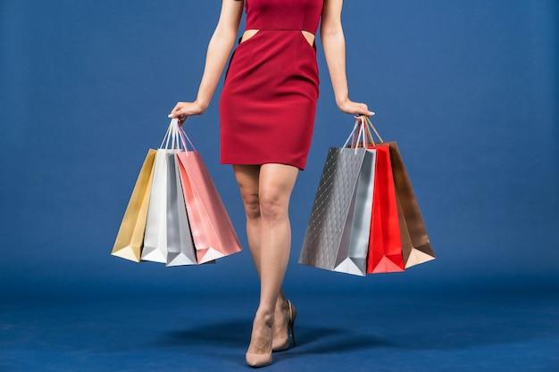 青い色でマルチカラーの買い物袋を運ぶ幸せな若いアジアの女性の足をクローズアップ