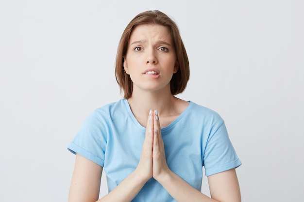 Closeup of upset worried young woman in blue t shirt keeps hands folded in praying position