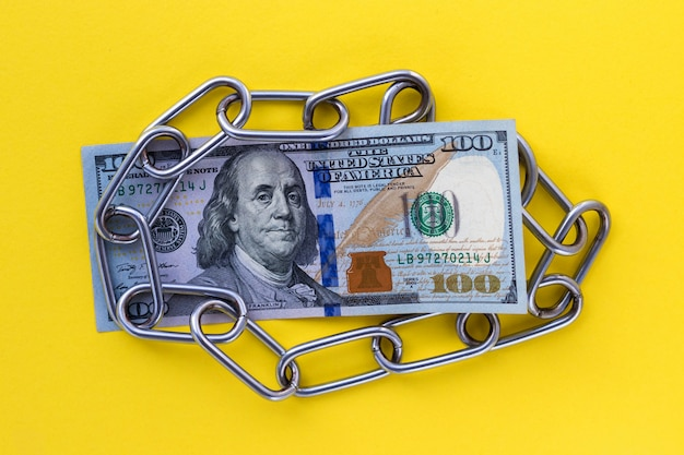 Closeup of us 100 hundred dollar under metallic chain on yellow background