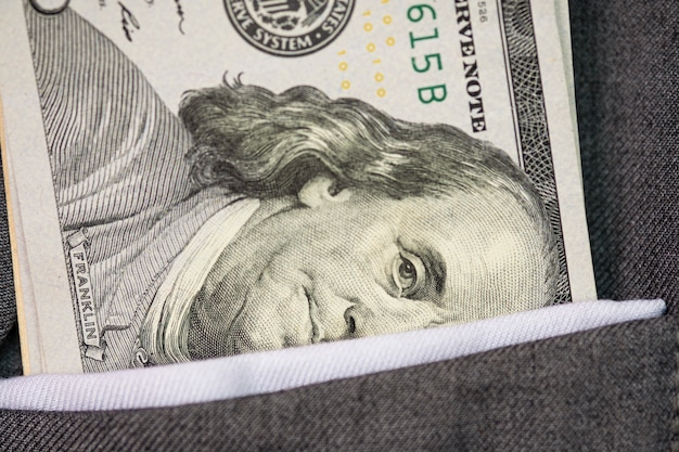 Closeup of us dollar banknote into grey suit pocket. investment and payment concept.