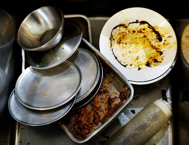 Closeup of used dishes and trays in restaurant kitchen sink