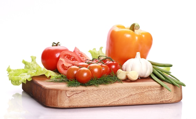 Closeup of various fresh and tasty vegetables on a wooden cutting board