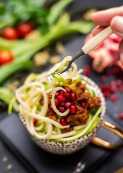 Primo piano di un pasto vegano con zucchine a spirale, salsa di pomodoro e melograni in tazza
