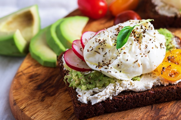 Closeup vegetarian toast with poached egg, cottage cheese, avocado and vegetables, light snack, healthy breakfast concept