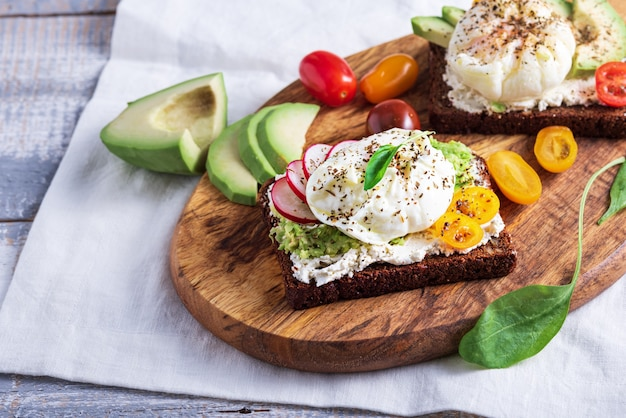 Closeup vegetarian toast with poached eggs, cottage cheese, avocado and vegetables on wooden board