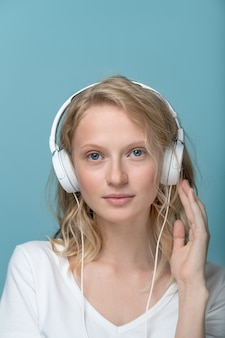 Крупным планом вертикальный портрет молодой женщины с закрытыми глазами, слушающей музыку