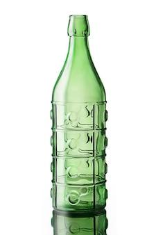 白い背景で隔離の緑のガラス瓶のクローズアップ垂直ショット
