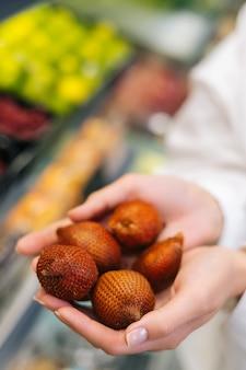 신선한 리치 과일을 손에 들고 있는 알아볼 수 없는 젊은 성인 여성의 클로즈업 세로 샷