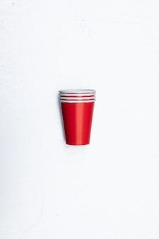 Colpo verticale del primo piano del set di bicchieri di carta rosso isolato su uno sfondo bianco