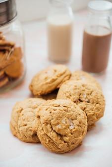 Colpo verticale del primo piano dei biscotti saporiti su una superficie bianca con latte al cioccolato