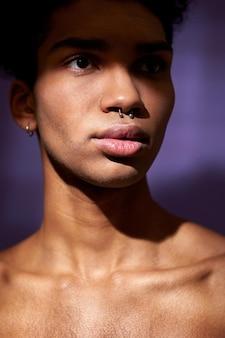 紫色の背景のヒスパニックモデルに筋肉の首を持つフィットの若い男のクローズアップverticale肖像画