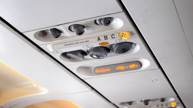 Closeup view of air ventilation system and reading lamps on airplane ceiling.