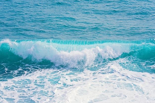 Closeup view of aquamarine rolling waves with splash