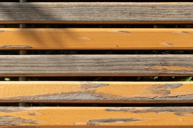 Closeup view of the bench with partly chipped paint on the planks