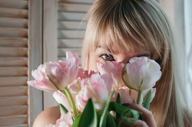 A closeup view of a blonde woman with pink flowers