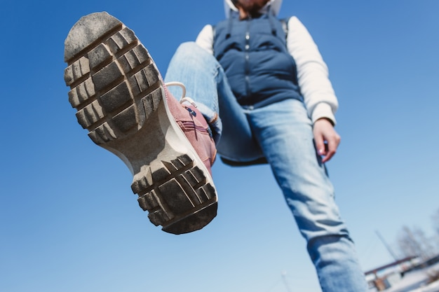 Closeup view of the bottom of the sole young teen girl in jeans and hoodie lifts her foot stepping on camera against the blue sky