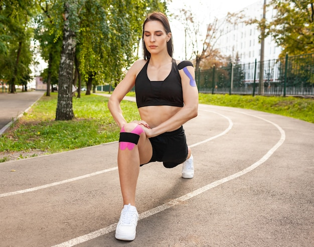 Closeup view of bruette flexible woman with muscular body warming up outdoors, practicing deep lunges. stunning fit young sportswoman training in summer park, wearing kinesiology tapes on knees.