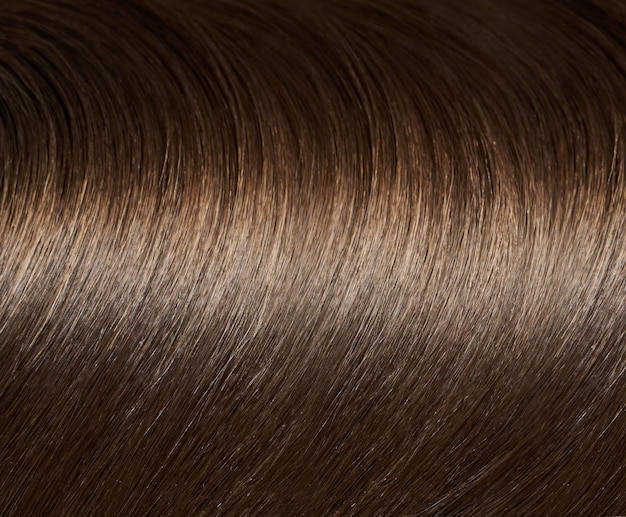 A closeup view of a bunch of shiny straight brown hair in a wavy curved style