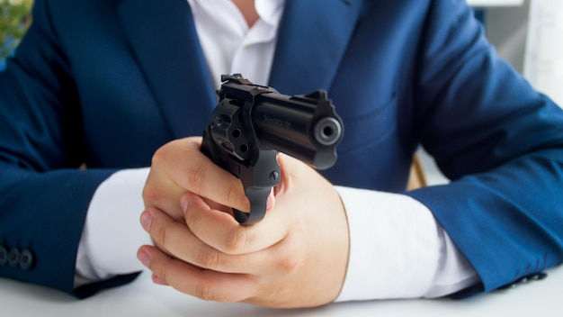 Closeup view of businessman in suit sitting behind desk and aiming with gun