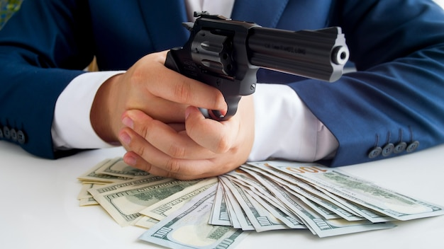 Closeup view of businessman with wad of cash aiming with gun
