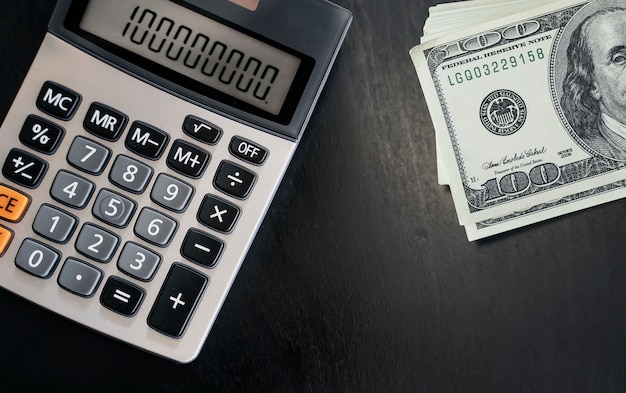Closeup view of calculator and banknotes on dark wooden table.