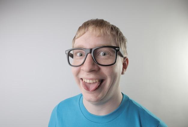 Vista del primo piano di un maschio caucasico che indossa una maglietta blu e occhiali da vista che fanno i gesti divertenti del fronte