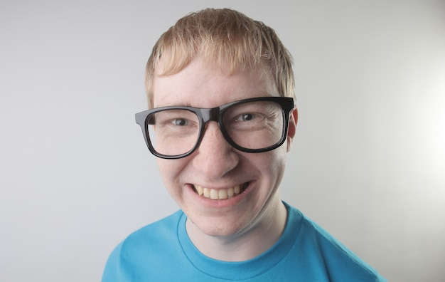 Closeup view of a caucasian male wearing a blue t-shirt and eyeglasses making funny face gestures