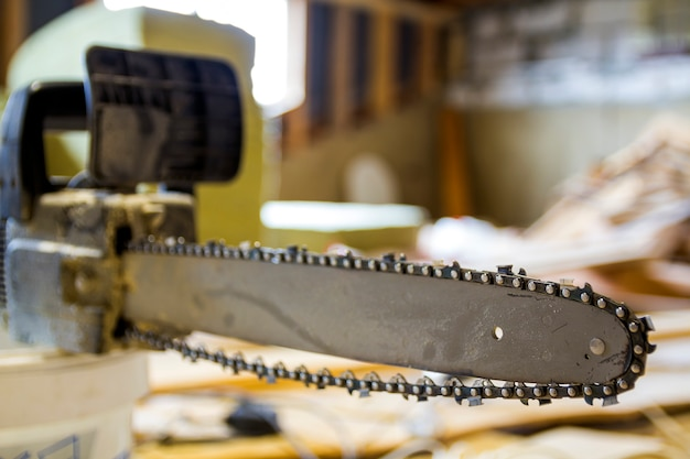 Closeup view of a chainsaw bar and cutting chain at construction site