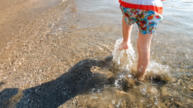 Closeup view of child's feet running in sea water on beach.