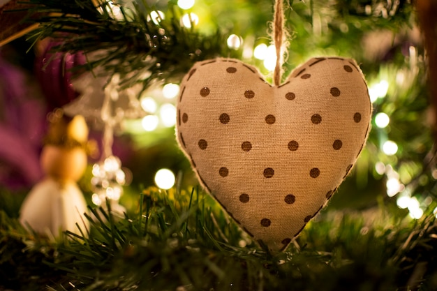 Closeup view of a christmas tree ball with a heart shape and lights from inside the tree
